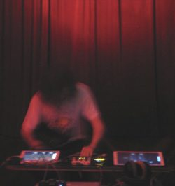An atmospheric dark, blurred photograph shows Robbie in action making music using technology, performing in front of a red velvet curtain
