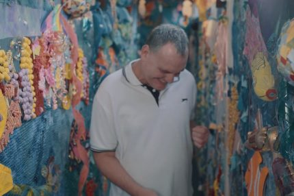 A man looks down and smiles as he dances in a colourful space decorated with papier mache
