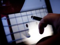 A hand holding an electric pen hovers over an ipad with a guitar fret visible on the screen