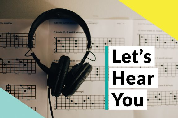 The words Let's Hear You overlaid on an image of headphones on sheet music