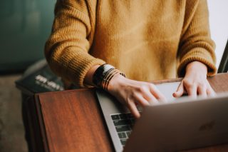 Woman wearing mustard jumper uses a laptop