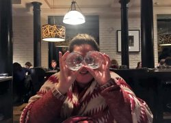 Sonia holds two glasses up to her face, like eyes