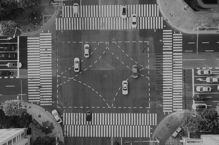 A view of a city crossing from overhead, grids and people and cars