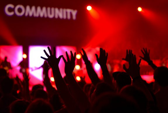 Hands reach into the air, a band is onstage and we can see the word 'community' above them