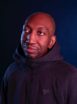 Dike wears a Nike hoodie and looks off camera with a soft, slightly smiling expression. Shot inn low light against a dark backdrop, the image has a rich tone.