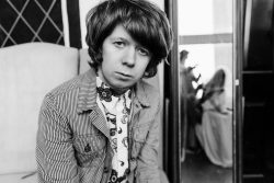 A black and white photo of James wearing stylish sixties clothing. He has a mop top hair cut and looks at us quizzically.