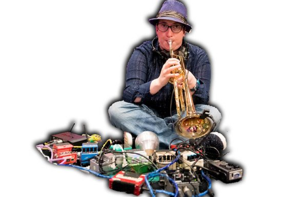 Robyn sits cross legged wearing jeans and a purple trilby as she plays trumpet surrounded by pedals and wires