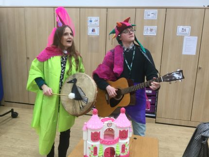 Two musicians play instruments, both are wearing eccentric brightly coloured clothes.