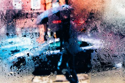 A person is seen through a rainy window, walking down the street holding an umbrella
