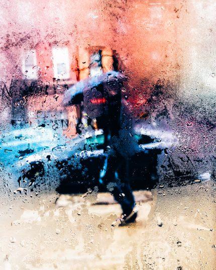 A person is seen through a rainy window, walking down the street holding an umbrella