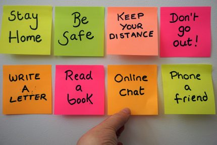 Neon post it notes saying Be Safe, Keep your Distance, Online Chat, with a hand reaching out to one.