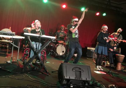 A band onstage wearing christmas hats and the lead singer has his hand in the air
