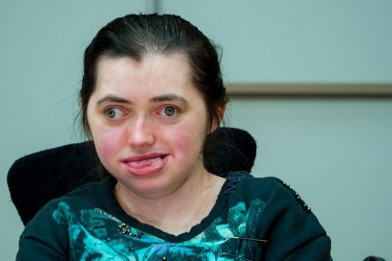 Lucy is a young white disabled woman with dark hair. Her