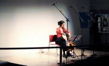 A cellist sits alone on a wide stage, lit brightly