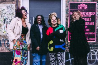 Four women of colour stand together in front of live music posters. They are dressed in colour, pattern and black and are smiling and joking.