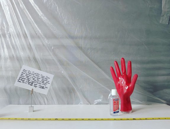 A red rubber glove stands up on a plain surface, with antibacterial gel on and next to it. This looks like a strange laboratory of some kind with plastic sheeting and measuring implements around.