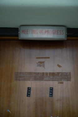 An unlit light above a door says 'meeting in progress', the door looks slightly abandoned with old tape and fixtures on it.