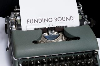 An old fashioned typewriter with 'funding round' written on the paper inserted into it