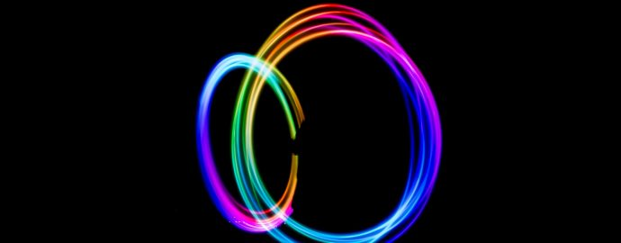 Two roughly circular swirls of rainbow light on a black background