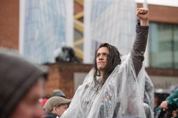 Jova is a young latinx person who is standing in a rain poncho with one fist raised aloft.