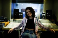 Joy smiles as she leans back against a mixing desk in a studio. She is a young white woman with curly dark hair.