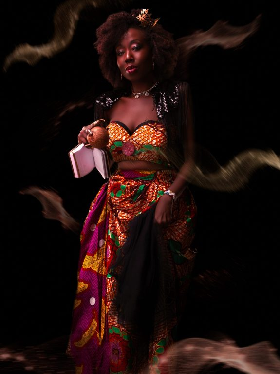Radikal Queen is a young black woman wearing a skirt and top made from brightly-coloured traditional African wax print fabric. She has an afro and wears a small crown and a slight smile.