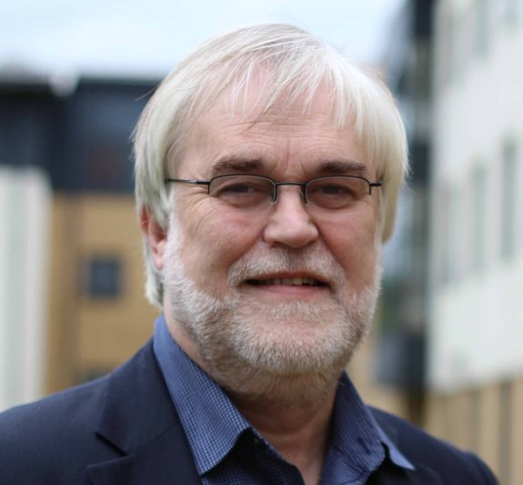 Adam is a white man wearing a navy blazer and shirt. He has white grey hair and beard and wears small wire frame glasses.