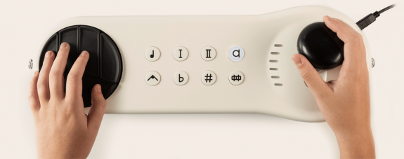 A cream coloured instrument with a black joystick at one end and a trackpad at the other. There are 8 buttons inbetween with different symbols on.