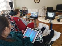 Two Disabled women are playing music using technology. One plays an iPad the other makes music using her eyes with a computer.