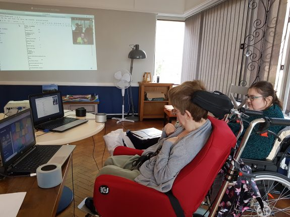 A room in a care home, two women are engaged in a music-making session via zoom.