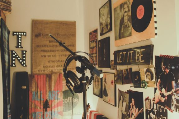 A music room, with photographs and posters taped to the wall, headphones hanging on a mic stand.