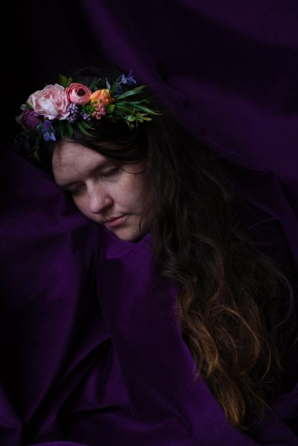 Elinor is wrapped in a rich purple velvet cloth, she has her eyes closed and her head turned to the side, pressing her cheek to the fabric. She is a white woman wearing a crown of flowers with long brown hair.