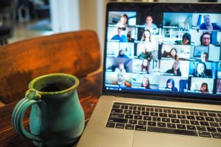 A mug and computer screen with zoom event visible