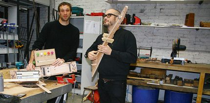Two white men in a workshop environment are striking funny poses to show off unusual instruments they have built