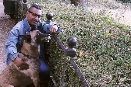 An asian man wearing a denim jacket, smiling as he crouches down and strokes a large dog