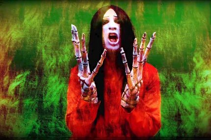 Still from a music video showing a man with a pale fave and long black hair, his hands are like large skeleton hands.