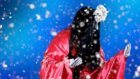 A figure with long black hair and a red robe against a blue background, very high contrast. There is snow coming down in front.
