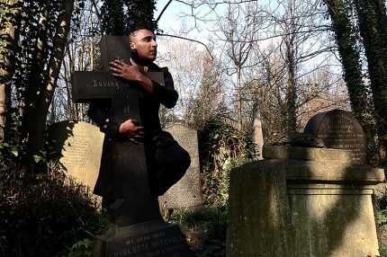 Patrick stands in a graveyard lit by sunlight. He wears a smart coat and has black hair