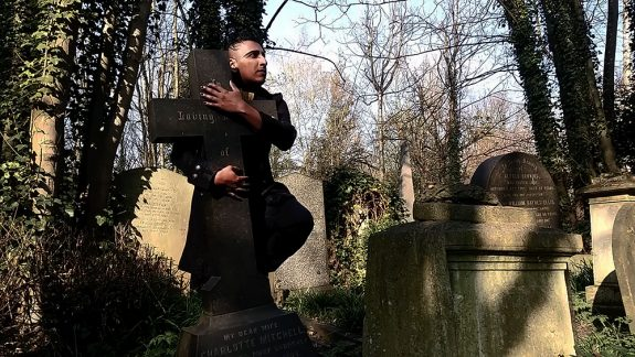 Patrick stands in a graveyard lit by sunlight. He wears smart clothes and has black hair, long on top and shaved at the sides. He embraces a cross and looks into the distance.