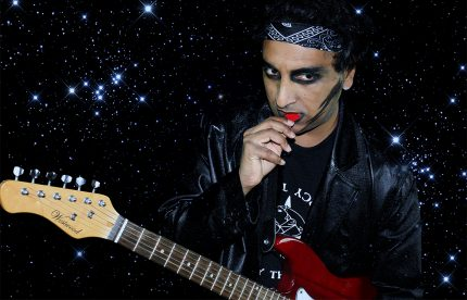 Musician Patrick is wearing a bandana and black eyeliner, holding an electric guitar and pick.