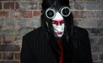 A man with black hair, his face painted white with a red stripe across the eyes and black liner. He is wearing dark goggles on his head and looking up at the camera with a hint of menace.