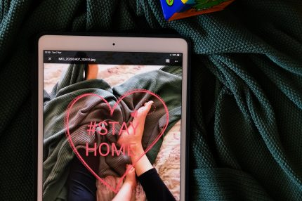 A tablet with the words Stay Home on the screen and a child's cube shaped toy