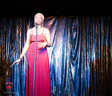 Tobi stands onstage in front of a shiny curtain. Their hair is a short platinum afro and they are singing into a mic.