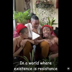 """A still from a video with a play button visible. Three people of colour are sitting closely together, singing. The lyrics are captioned and read """"in a world where existence is resistance"""""""