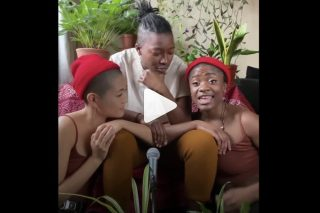 A still from a video with a play button visible. Three people of colour are sitting closely together, singing. The lyrics are captioned and read