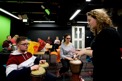 A workshop leader is supporting a young Disabled musician with a percussion instrument similar to bongos