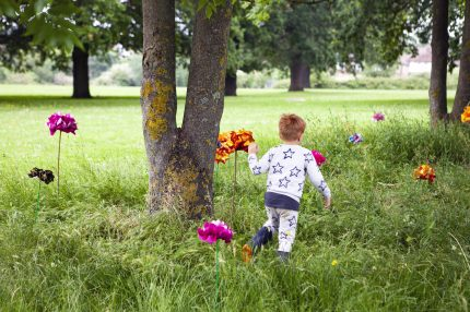 A child in the park runs through long grass, where silk flowers have been installed in bright colours