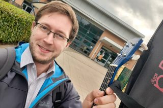 A white man in front of a school holds up a guitar and smiles as he takes a selfie