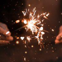 Hands hold sparklers, lighting them up
